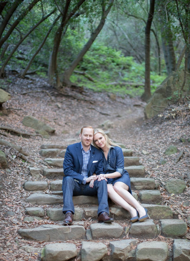 Portrait of stylish couple seated on Nojoqui Falls trail during engagement session.