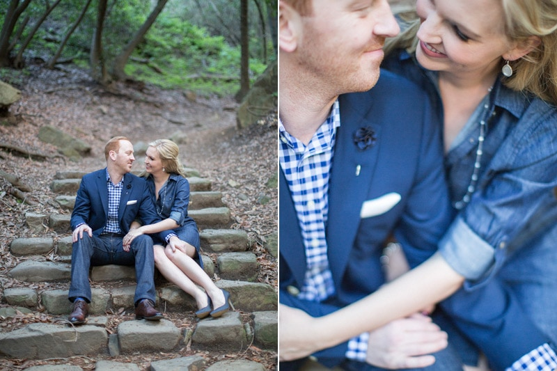 Stylish couple seated on Nojoqui Falls trail during engagement session.